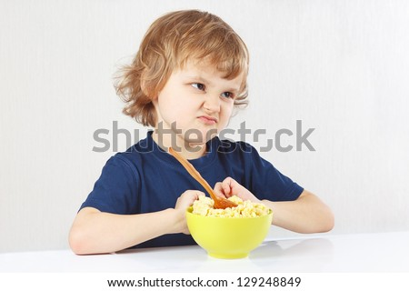 Little cute blonde boy refuses to eat a porridge - stock photo