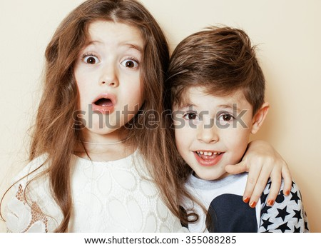 little cute boy and girl hugging playing on white background, happy family smiling brother and sister - stock photo
