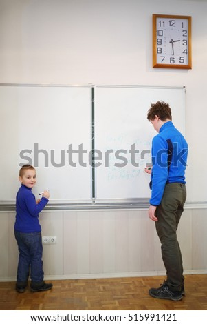 Little cute boy and teen stand near blackboard with formulas in classroom
