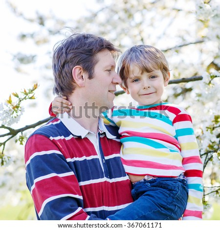 Little cute boy and young father hugging in blooming cherry garden in spring. Happy family celebrating father's day.a - stock photo