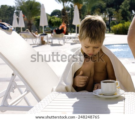 little  cute boy at swimming pool warmed up with towel and hot tea, hotel background - stock photo
