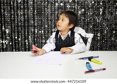 little cute boy draws on a desk - stock photo
