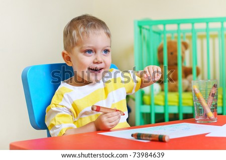 Little cute boy draws with crayons in the nursery - stock photo