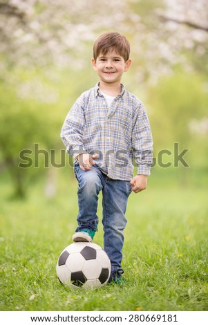 Little cute boy dressed casual playing with soccer ball in summer park.