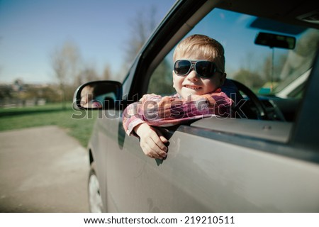 little cute boy driving fathers car at springtime - stock photo