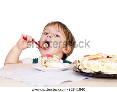 Little cute boy eating a cake. Isolated on white - stock photo