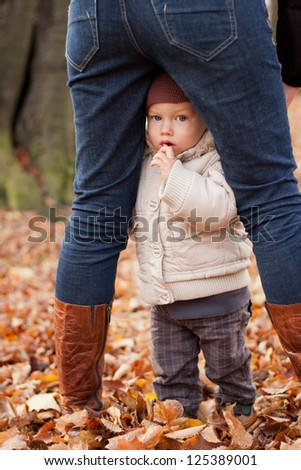 Little cute boy hiding behind his mother's legs - stock photo