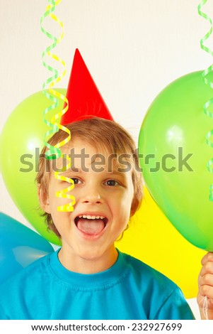 Little cute boy in festive hat with holiday balls and a streamer