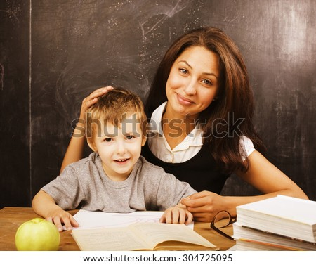 little cute boy in glasses with young real teacher, classroom studying at blackboard school - stock photo