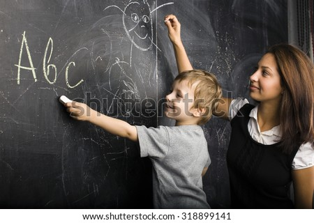 little cute boy in glasses with young real teacher, classroom studying at blackboard school kido close up - stock photo