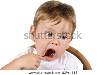 Little cute boy in white eating jam with a spoon. Isolated on white.