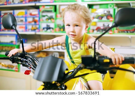 Little cute boy in yellow sits on toy motorcycle in store with toys. - stock photo