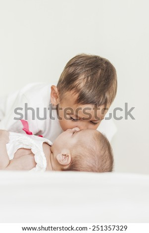 Little Cute Boy Kisses His Lovely Newborn Sister. Vertical Image - stock photo