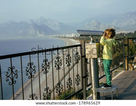 little cute boy looking through telescope at sea viewpoint in Ataturk park - stock photo