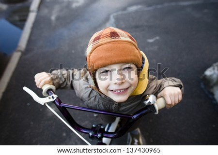 little cute boy on bicycle smiling close up - stock photo
