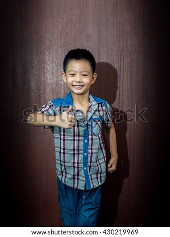 little cute boy on wood background gesture smiling closeup, thumbs up - stock photo