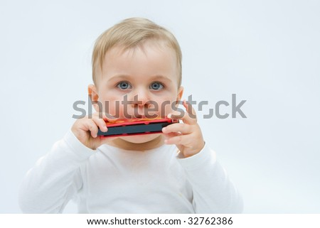 little, cute boy playing harmonica, on white