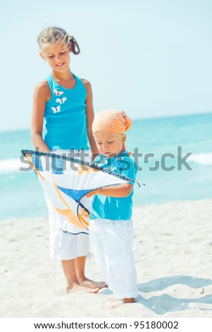 Little cute boy playing his sister with a colorful kite on the tropical beach. Verticl view