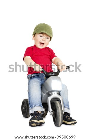 Little cute boy playing on a plastic motorcycle. - stock photo