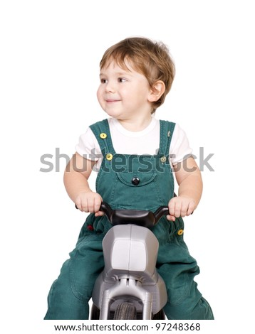 Little cute boy playing on a plastic motorcycle. Isolated on white. - stock photo