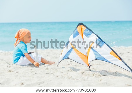 Little cute boy playing with a colorful kite on the tropical beach. - stock photo