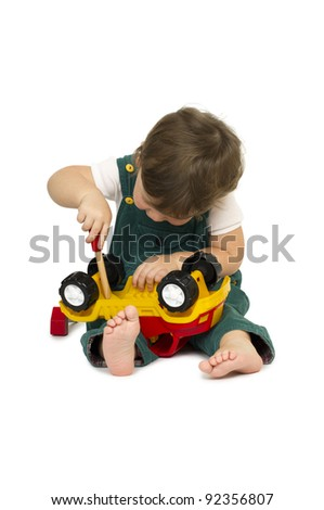 Little cute boy playing with a plastic toy truck. - stock photo