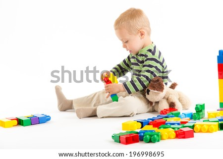 Little cute boy playing with plastic building blocks and plush puppy. Isolated on white. - stock photo