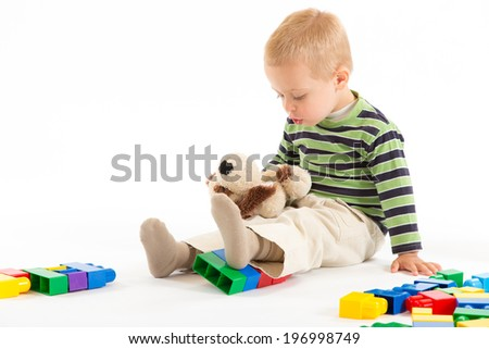 Little cute boy playing with plastic building blocks and plush puppy. Isolated on white.