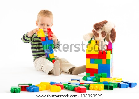 Little cute boy playing with plastic building blocks. Isolated on white. - stock photo