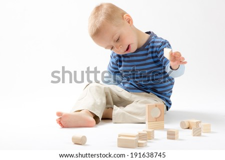 Little cute boy playing with wooden building blocks. Isolated on white. - stock photo