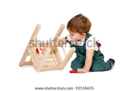 Little cute boy repairing a chair. Isolated on white. - stock photo