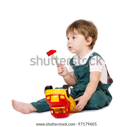 Little cute boy repairing a plastic toy truck. Isolated on white. - stock photo