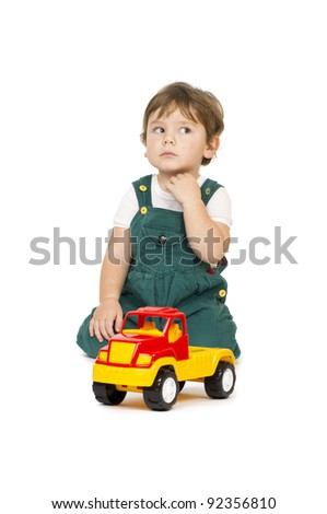 Little cute boy sitting behind a plastic toy truck. - stock photo
