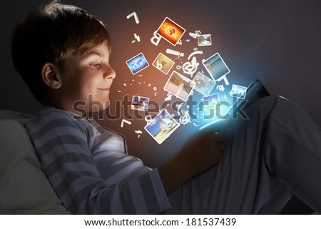 Little cute boy sitting in bed and using tablet - stock photo