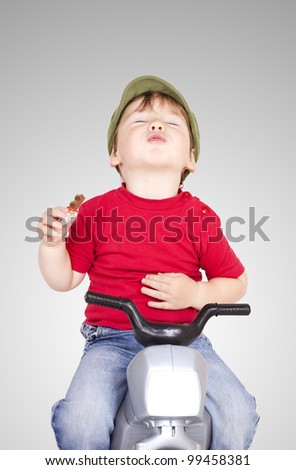 Little cute boy sitting on a plastic motorcycle eating a chocolate. - stock photo