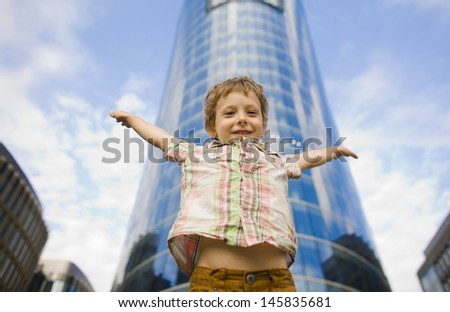 little cute boy standing near business building, smiling - stock photo