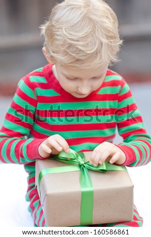 little cute boy unwrapping his christmas present, shallow DOF, focused on hands and present - stock photo