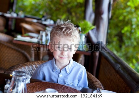 little cute boy waiting for his breakfast at the hotel - stock photo