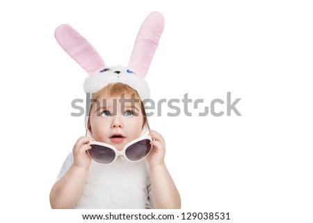 Little cute boy with big blue eyes dressed in Easter bunny ears take off sunglasses and looking up. Little Easter bunny on white background. - stock photo