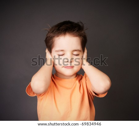 Little cute boy with closed eyes and stop one's ears, studio shot - stock photo