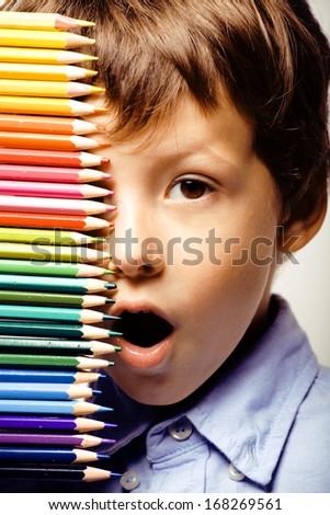 little cute boy with color pencils close up smiling - stock photo
