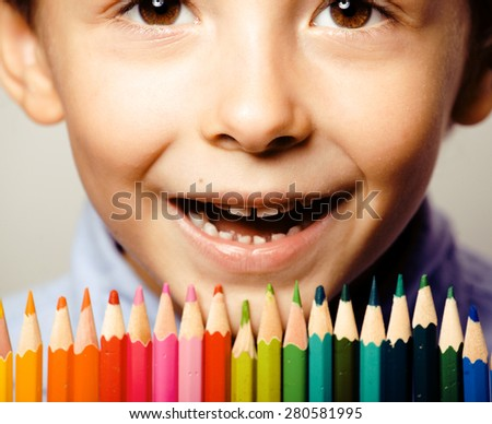 little cute boy with color pencils close up smiling, education face colored - stock photo