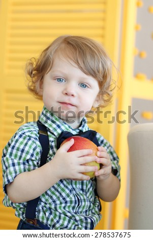Little cute boy with curly hair holds apple and looks at camera - stock photo