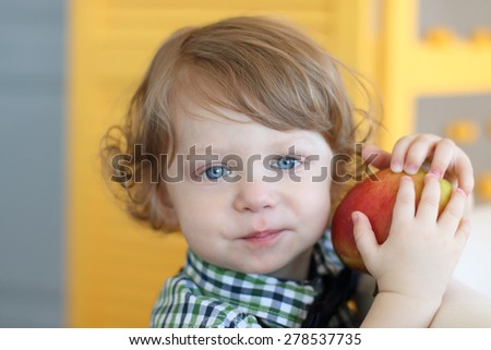 Little cute boy with curly hair holds red apple and looks at camera - stock photo