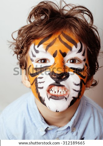 little cute boy with faceart on birthday party close up, orange tiger - stock photo
