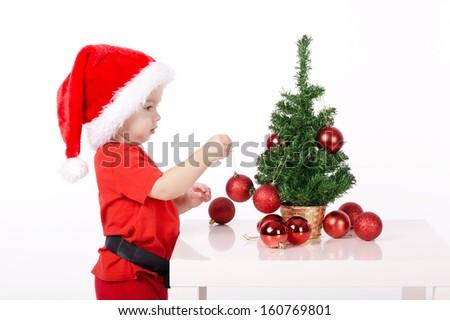 little cute boy with Santa hat decorates christmas tree - stock photo