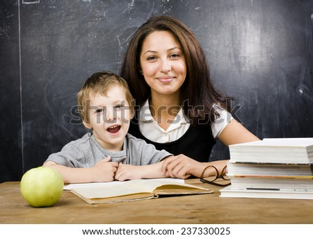 little cute boy with teacher in classroom smiling - stock photo