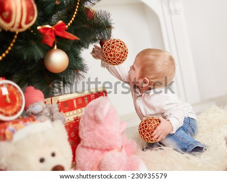 Little cute boy with white hair playing with Christmas toys - stock photo