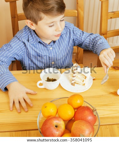 little cute boys eating dessert on wooden kitchen. home interior. smiling adorable