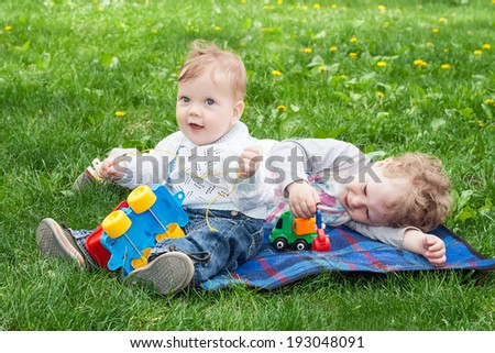 Little cute brothers playing on the grass - stock photo